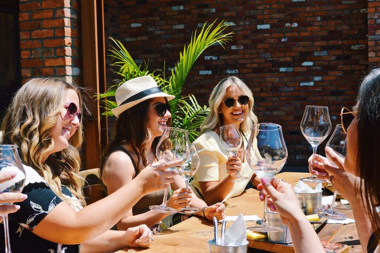 A group of women drinking wine in the sun.